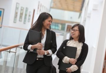 Two girls walking down an office corridor